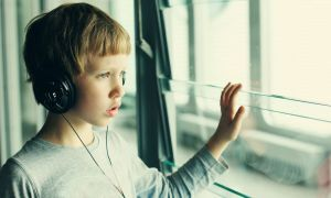 A boy with headphones on looks out the window.