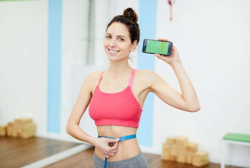 smiling-woman-presenting-weightloss-app